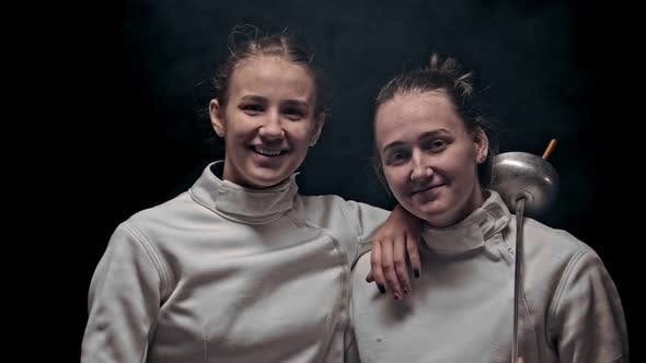 Thumbnail for Two Young Women Fencers Standing in the Dark Studio - Looking in the Camera