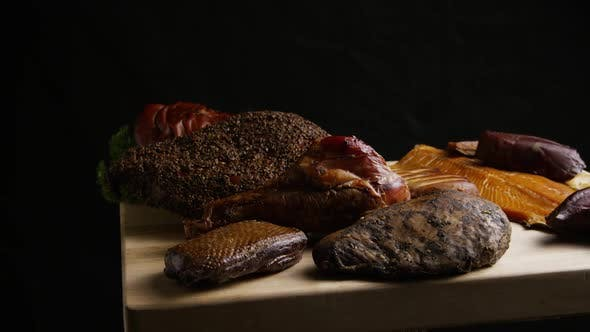 Rotating shot of a variety of delicious, premium smoked meats on a wooden cutting board