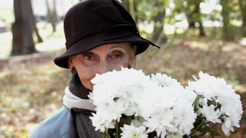 Happy Elderly Woman in Coat and Hat Sniffing a Bouquet of Flowers and Smiling