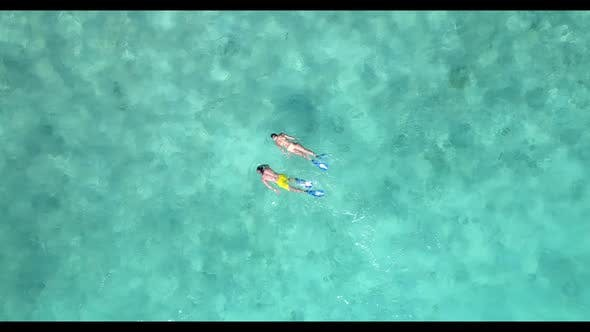 Thumbnail for Two people tanning on tranquil resort beach holiday by transparent lagoon and white sand background