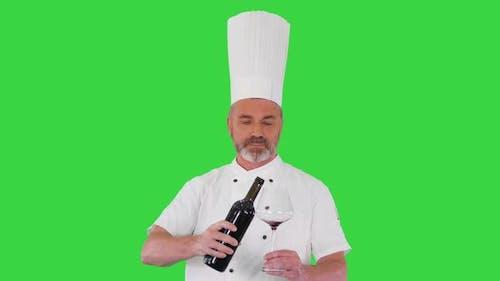 Senior Man Cook Tasting Red Wine on a Green Screen Chroma Key