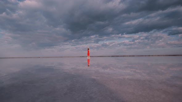 Thumbnail for Tourist Girl Is Walking Along a Salt Lake in Which Clouds Are Reflected