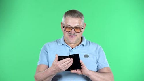 Portrait of Aged Man Talking for Video Chat Using Mobile Phone, Isolated Over Green Background
