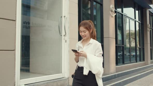 Businesswoman using smart phone and typing message while walking alone outdoors in urban city