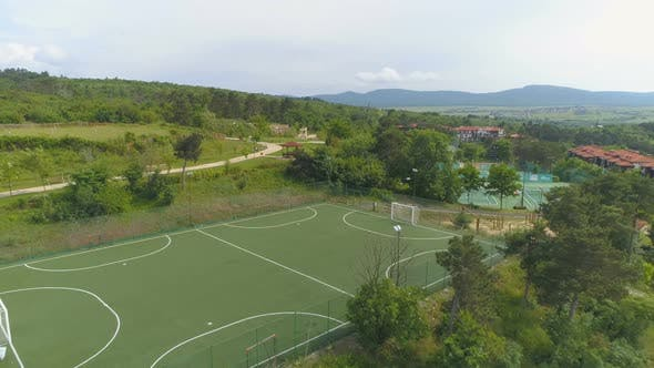 Cover Image for Aerial above Football field and tennis courts in luxurious resort