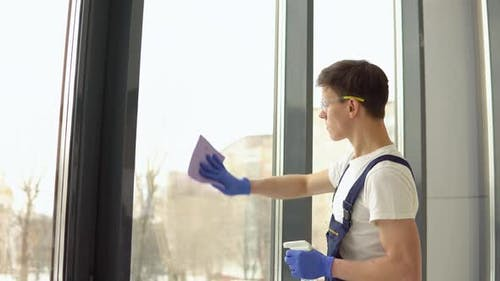 Young Serviceman in Protective Uniform and Glasses Washes Windows
