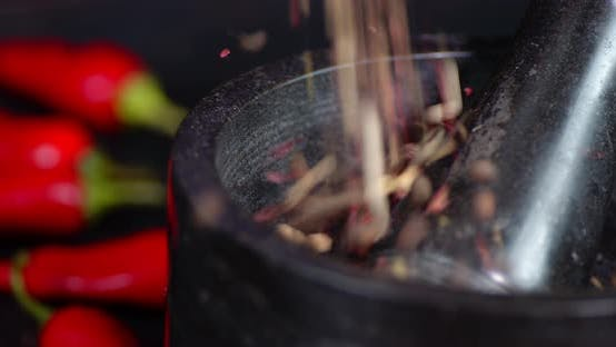 Peppercorns Falling Into Mortar with Pestle