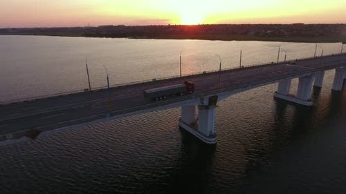 Aerial Shot of a Stretched Bridge Over the Dnipro at Impressionist Sunset in Summer
