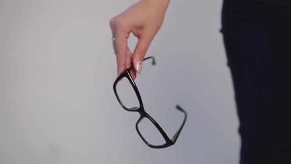 Thumbnail for Female Hand is Holding Model of Eyeglasses with Black Rim