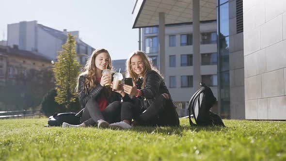 Cover Image for Young Caucasian Women Drinking Fresh Juice while Sitting on the Green Grass Using Mobile Phone