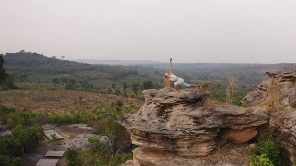 Thumbnail for Drone Shot of a Woman By the Large Rock in the Mountains Doing Yoga Exercises