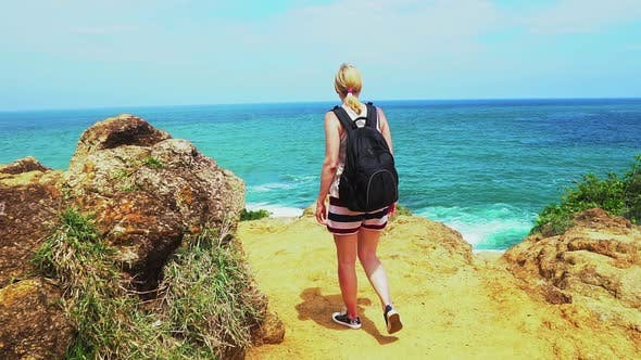 Thumbnail for traveler girl walking along the shore of the tropical sea. beautiful seascape with rocks