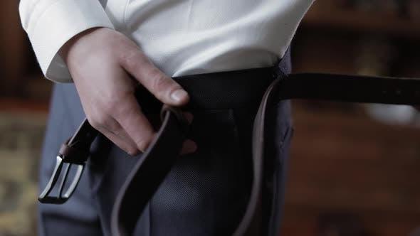 Thumbnail for Hübscher Bräutigam fixiert seinen Gürtel mit Hose. Hochzeitsmorgen. Geschäftsmann