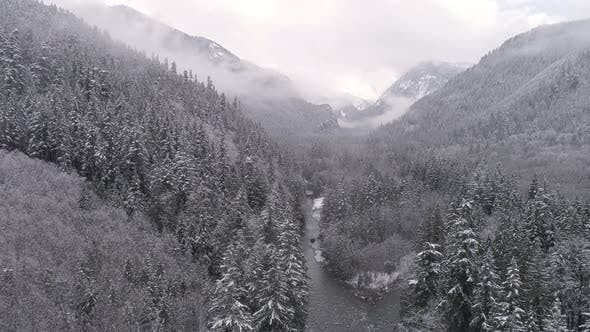 Thumbnail for Aerial Pan Of Beautiful Mountain Forest Valley With Snowfall On Ice Cold River In Frozen Landscape