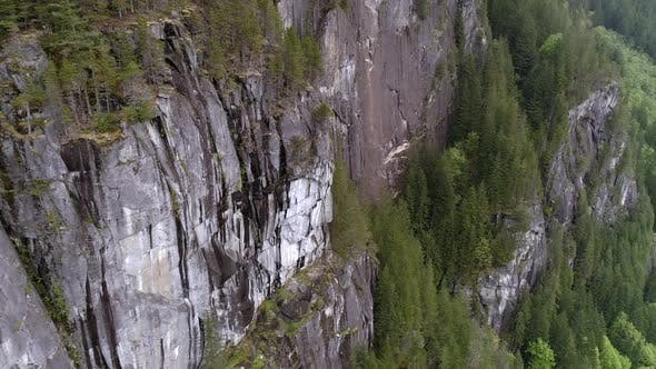 Thumbnail for Helicopter View Of Massive Mountain Cliffs In Pacific Northwest Wilderness With Evergreen Forest