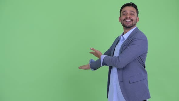 Cover Image for Happy Young Bearded Persian Businessman Presenting To the Back