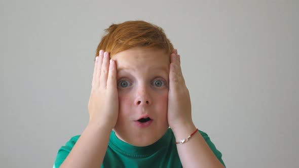 Gros plan de l'adorable garçon rouge saisissant sa tête et montrant de la joie sur son visage