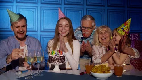 Happy Birthday Woman Blowing Candles on Cake Making Wish Having Fun Celebrating Party with Family