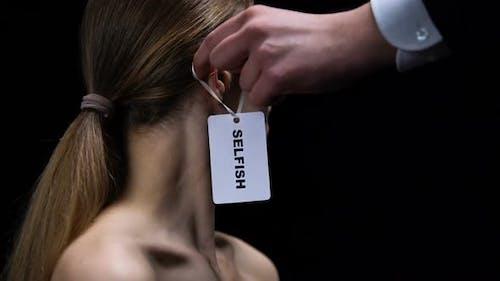 Männliche Hand legt selbstsüchtige Marke auf weibliches Ohr, Selbstversorgung und Unabhängigkeit