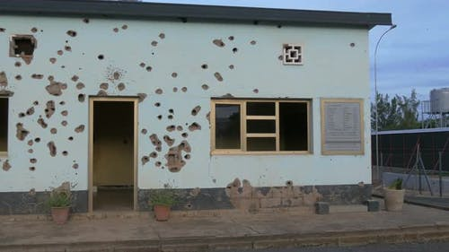 Bullet holes on wall in Kigali Camp