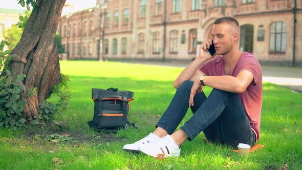 Thumbnail for Young Man Sits Near the Tree Has Phone Conversation