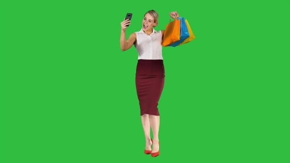 Thumbnail for Cheerful woman with shopping bags taking selfie on a Green