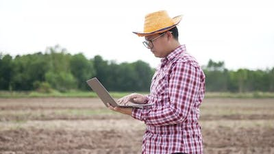 Smart farmer using laptop with tractor