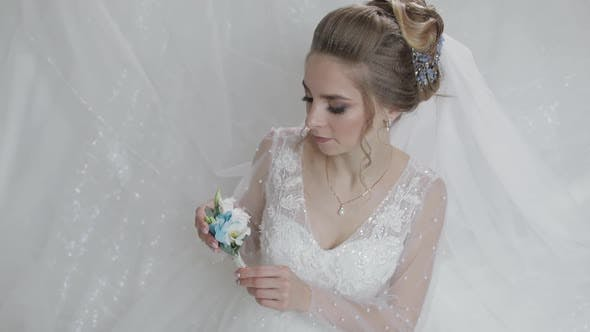 Thumbnail for Bride in Wedding Dress with Small Bouquet in Hand. Pretty and Well-groomed Woman