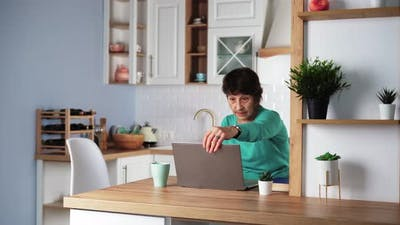 Elderly Focused Woman Remotely Working on Laptop at Home