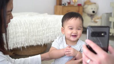 Infant Asian Boy with Mother Watching Video on Smartphone and Laughing
