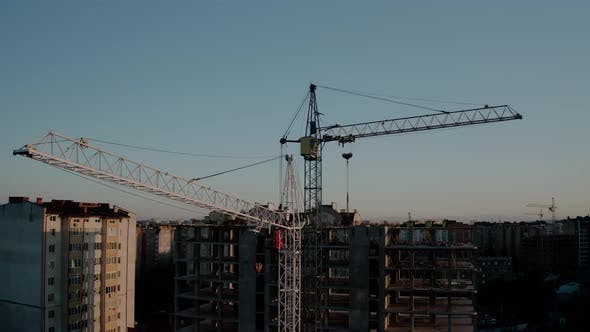 Thumbnail for Aerial Drone View of Construction Cranes in Sunset Light. Construction Site Building in City