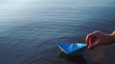 Paper ship in children hand. Blue paper ship. Beautiful sunset