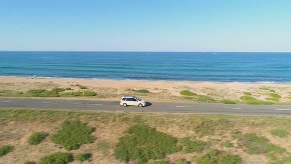 White Car Speeding on Straight Asphalt Coastal Road Against Blue Sea and Sand Beach