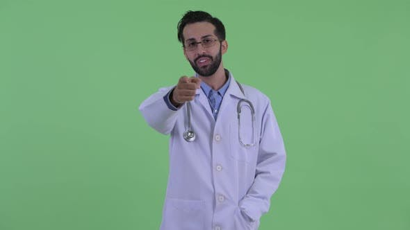 Thumbnail for Happy Young Bearded Persian Man Doctor Pointing at Camera