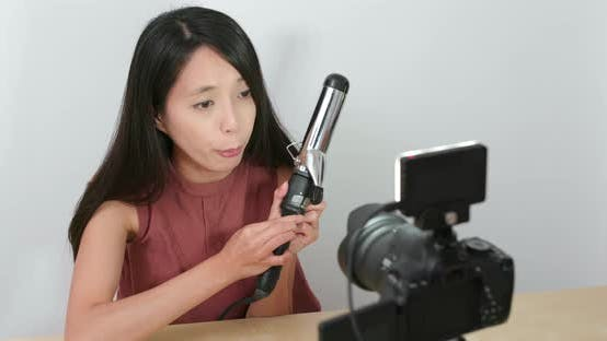 Thumbnail for Woman making hair in front of the digital camera to take vlog on social media