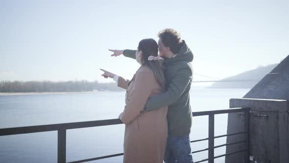Cover Image for Side View of Happy Couple in Love Chatting on River Bank and Pointing Away. Young Caucasian Man and