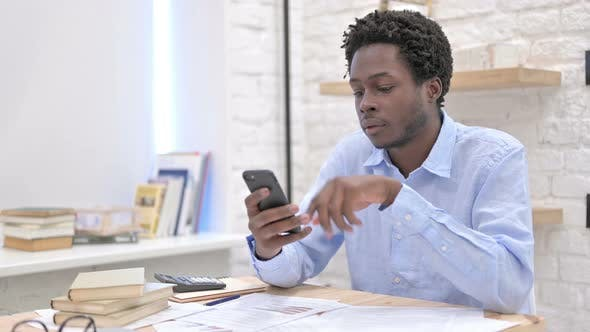 Thumbnail for Smart African Man Scrolling on Cellphone