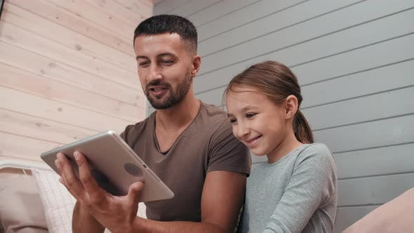 Cheerful Father and Girl Looking at Tablet