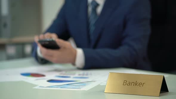 Busy Male Banker Using Smartphone, Working on Documents for Financial Statement