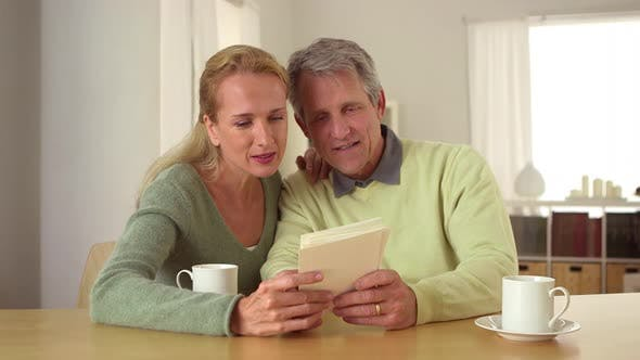 Thumbnail for Senior couple looking over photos