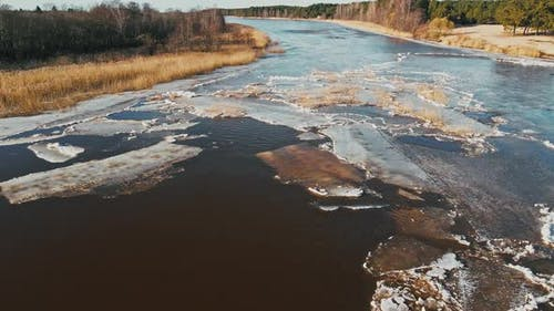 Low Flight Melting Snow and Ice at River Joining Sea in Spring Aerial