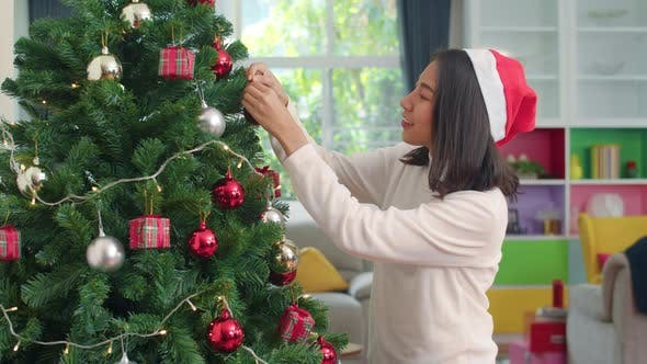 Female teen happy smiling celebrate xmas winter holidays in living room at home.