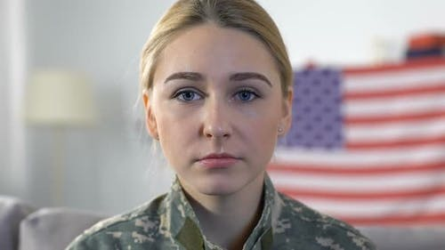 Sad Servicewoman Looking Camera With American Flag on Background, Memorial Day