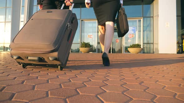 Thumbnail for Business Man and Woman Going To the Airport with Their Luggage. Young Businessman Carrying Suitcase