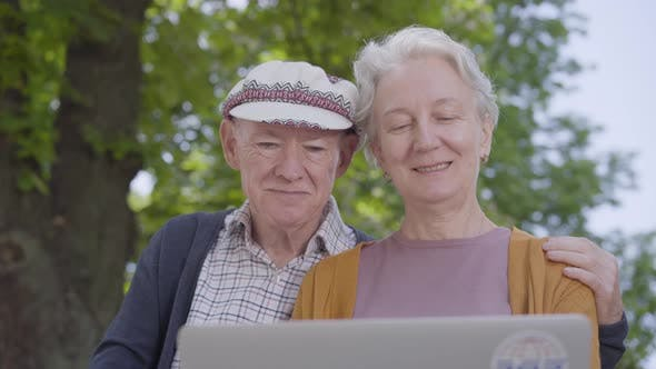 Thumbnail for Portrait Adorable Old Woman with Grey Hair and Old Man in Cap Sitting in the Bench in the Beautiful