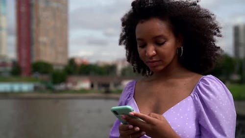 Black Woman Is Walking Outdoors and Browsing Social Nets at Smartphone