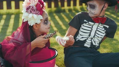 Kinder teilen ihre Süßigkeiten nach Trick oder Behandlung