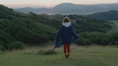 Back view of travel woman with dreadlocks near the tent standing on top of hill looking at sunrise.