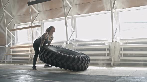 Thumbnail for Tattooed Female Athlete Flipping Tractor Tire