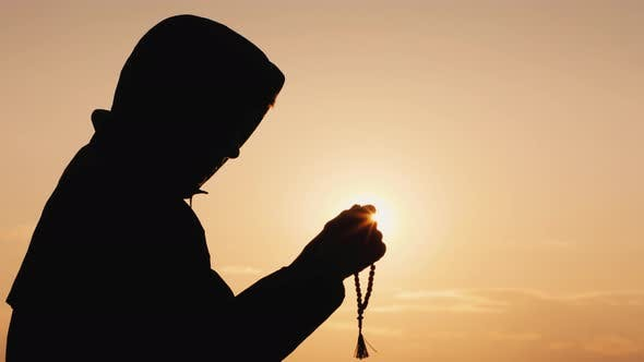 Thumbnail for Side View of a Man in the Hood, Sifting Through the Rosary at Sunset